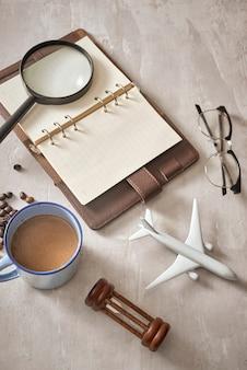 Reizen planning concept achtergrond. accessoires voor reizigers; vergrootglas, zonnebril, vliegtuig en notebook op houten tafel, bovenaanzicht en kopieerruimte copy