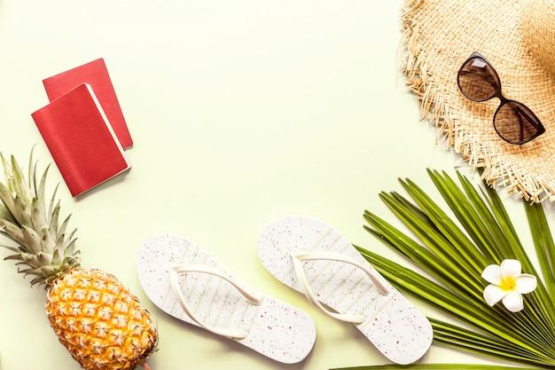 Reizen plat leggen items: verse ananas, twee paspoorten, grote strooien hoed, zonnebril, tropische bloem plumeria en palmblad.