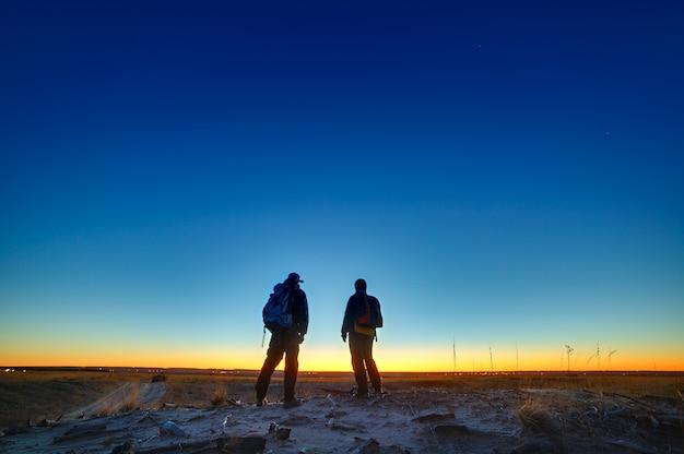 Reizen tijdens de schemering. toeristen op de weg tegen de achtergrond van een stralende zonsondergang en een wolkenloze hemel.