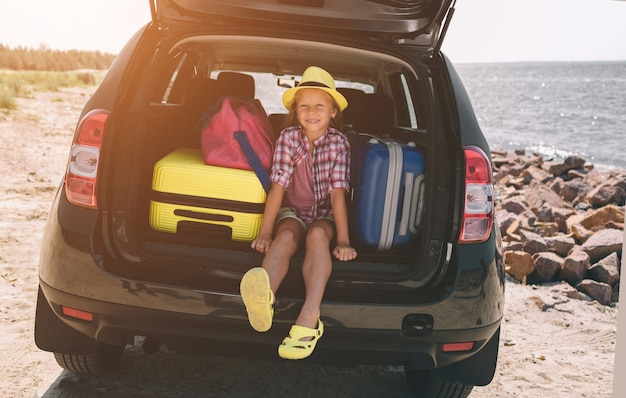 Reizen, toerisme - meisje met tassen klaar voor de reis voor zomervakantie. kind gaat op avontuur. auto reizen concept