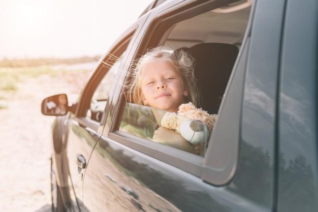 Reizen, toerisme - meisje met teddybeer klaar voor de reis voor zomervakantie. kind gaat op avontuur. auto reizen concept