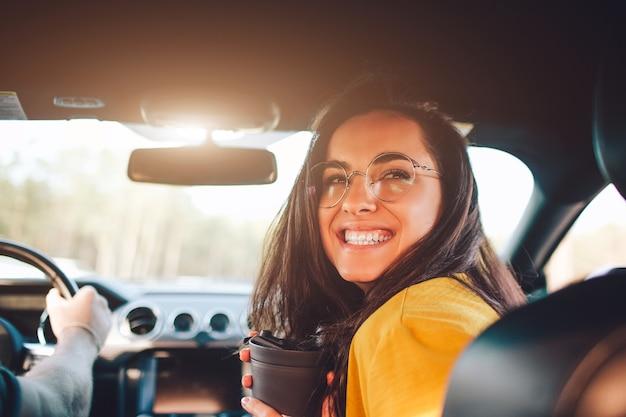 Reizen, toerisme - mooie vrouw met een paar thee of koffie lachend zittend op de stoel in de auto.