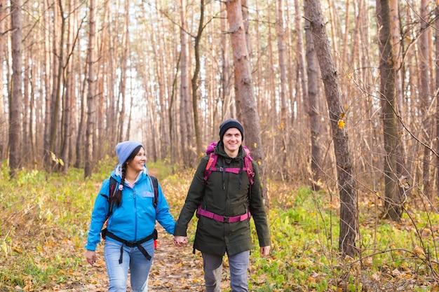 Reizen toerisme wandeling en mensen concept paar met rugzakken wandelen in de herfst bos