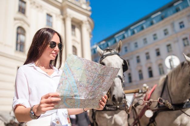 Reizen toeristische meisje met kaart in wenen buiten tijdens vakantie in europa,