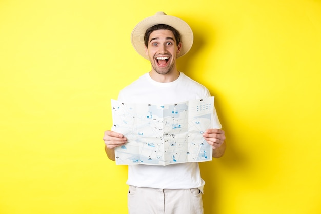 Reizen, vakantie en toerisme concept. opgewonden man toeristische gaan sightseeing met kaart, staande op gele achtergrond.