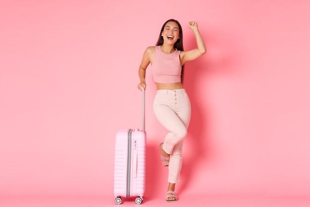 Reizen, vakantie en vakantie concept. de onbezorgde succesvolle aziatische meisjestoerist kwam met koffer op luchthaven aan