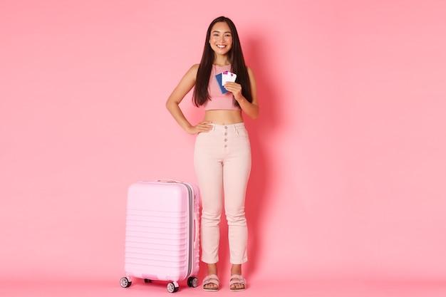 Reizen, vakantie en vakantie concept. full-length van vrolijke lachende aziatische meisjestoerist met koffer, paspoort met vliegtickets, op weg naar luchthaven om reis te beginnen, roze muur