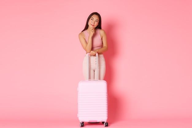 Reizen, vakantie en vakantie concept. nadenkend en nieuwsgierig aziatisch mooi meisje met koffer