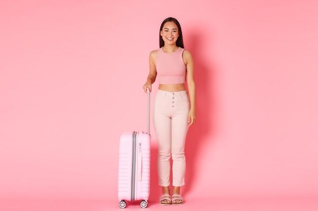 Reizen, vakantie en vakantie concept. portret van modieus aantrekkelijk aziatisch meisje dat zich voor reis klaarmaakt