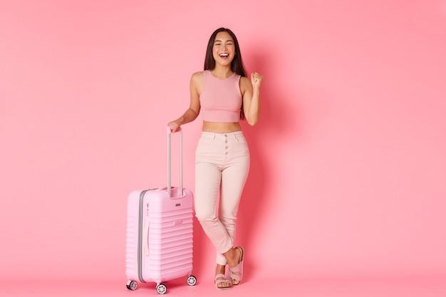 Reizen, vakantie en vakantie concept. van gemiddelde lengte van gelukkig aziatisch meisje dat zich voor vlucht klaarmaakt