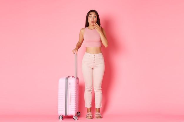 Reizen, vakantie en vakantie concept. verrast en hijgend schattig aziatisch meisje in zomerkleren