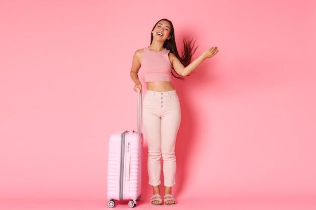 Reizen, vakantie en vakantie concept. zorgeloos en brutaal aziatische meisjestoerist ingepakte tassen om naar het buitenland te gaan