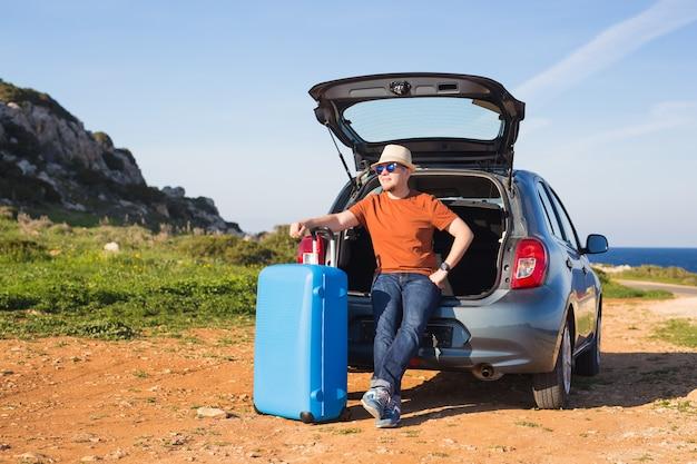 Reizen, vakantie, zomervakantie en mensen concept. man gaat op vakantie, koffers in de kofferbak van een auto.