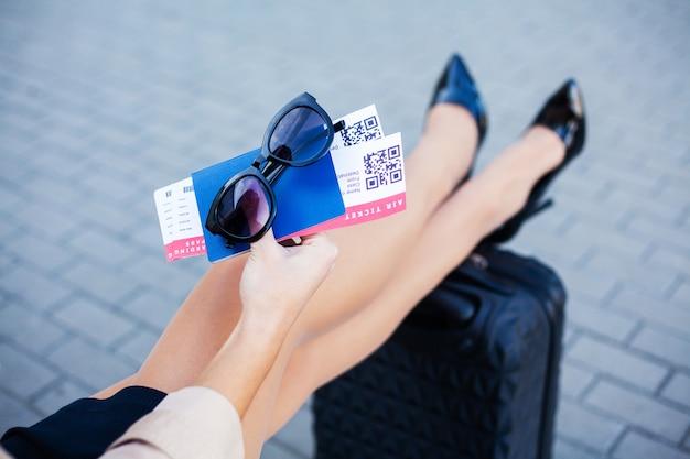 Reizen. vrouw die twee luchtkaartje in paspoort in het buitenland houden dichtbij luchthaven