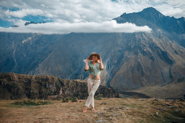 Reizen vrouw toeristische poseren tegen de achtergrond van de bergen en de bewolkte hemel.