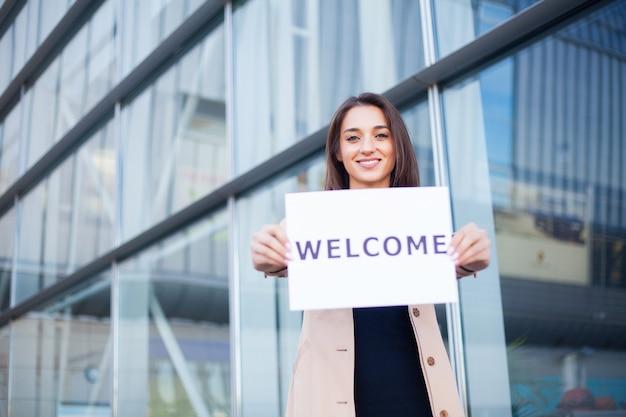 Reizen. vrouwenzaken met de affiche met welkomstbericht