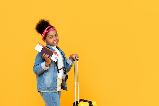 Reizend afrikaans amerikaans meisje met bagagepaspoort en instapkaart die op gele muur met exemplaarruimte wordt geïsoleerd