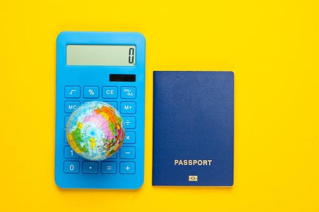 Reizend. berekening van de reiskosten rond de wereld. rekenmachine, wereldbol met een paspoort op geel