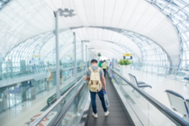 Reizend concept. aziatische reizigers die met bagage bij luchthaventerminal lopen en luchthaventerminal vage menigte van reizende mensen
