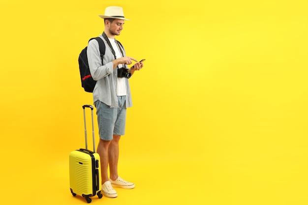 Reizend concept met jonge man op gele achtergrond, ruimte voor tekst.