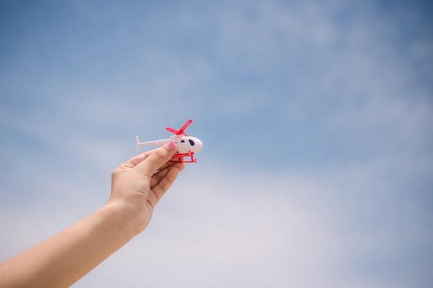 Reizend mensenconcept. hand die de helikopter op hemel toont
