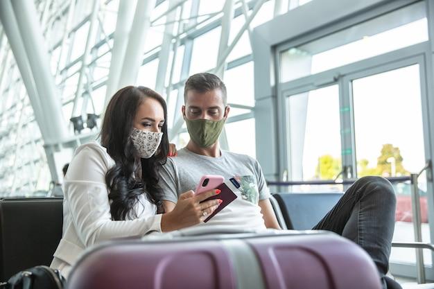Reizend stel met gezichtsmaskers controleert de laatste updates op een mobiele telefoon tijdens het wachten in een luchthaventerminal.