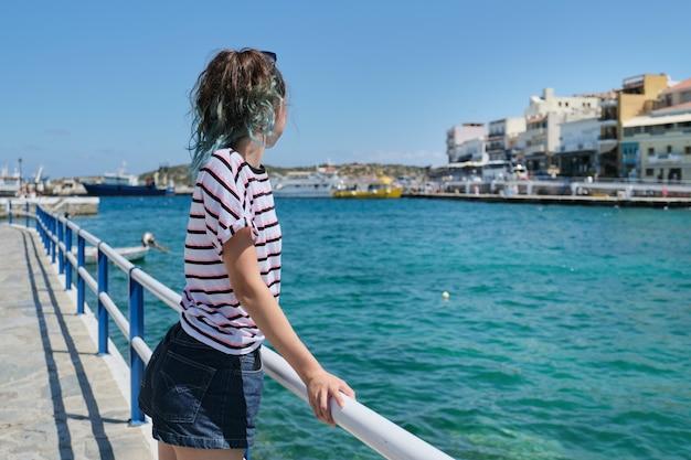 Reizend tienermeisje op zee baai mirabello geniet van schoonheid natuur