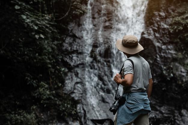 Reizende aziatische mannelijke toerist of fotograaf maakt een fotoreis naar een waterval in de natuur