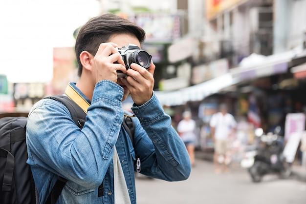 Reizende aziatische mannelijke toeristenbackpackers die foto in de weg van khao san, bangkok, thailand nemen