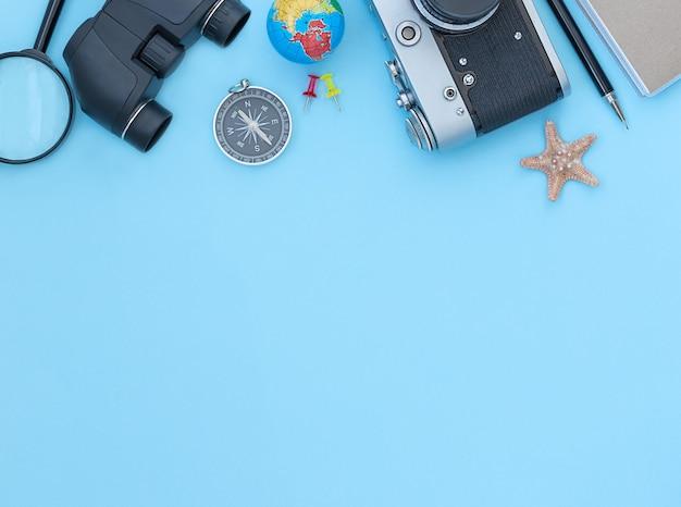 Reizende blauwe achtergrond met accessoires voor reiscamera verrekijker kompas pen globe vergrootglas notebook en ster