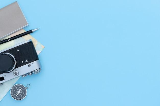 Reizende blauwe achtergrond met fotocamera, kompas, potlood, kaart en notitieboek met kopieerruimte