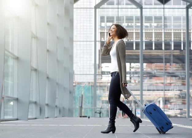 Reizende jonge vrouw met mobiele telefoon en koffer