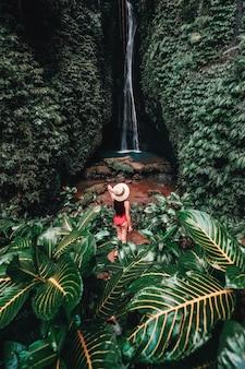Reizende jonge vrouw met tropisch regenwoud in bali genieten van het leven op prachtige lake lake waterval.