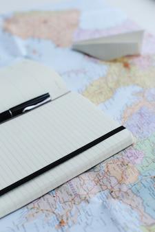 Reizende kaart, papieren vliegtuig en dagboek