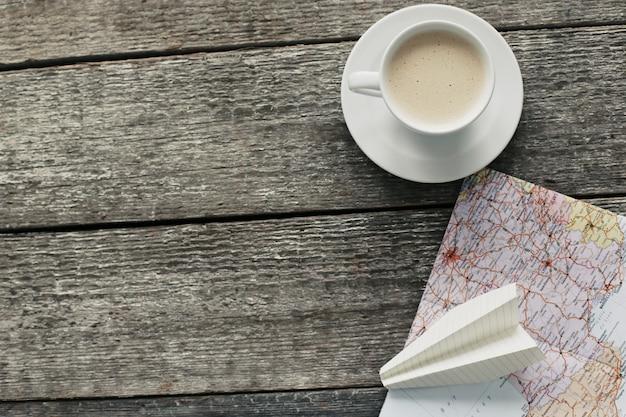 Reizende kaart, papieren vliegtuig en koffiekopje