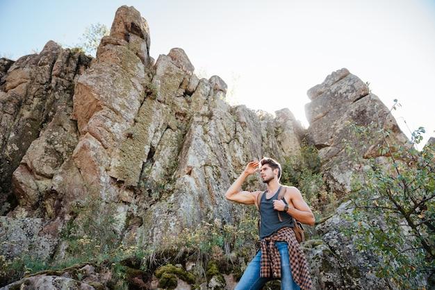 Reizende man met rugzak op rots wegkijken
