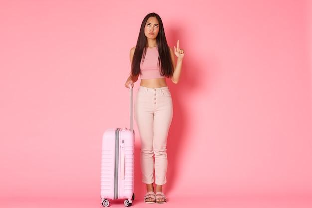 Reizende vakanties en vakantieconcept over de volle lengte van overstuur en teleurgesteld klagende meisjestoerist grimassen als kijken en wijzende vinger omhoog fronsend boos vasthouden koffer roze muur