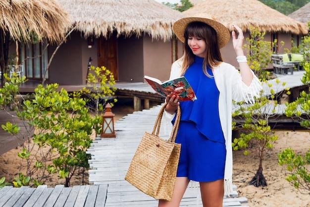 Reizende vrouw die en notitieboekje glimlacht bekijkt. blauwe jumpsuit, strohoed en tas, zonnebril. brunette meisje poseren in haar geweldige luxevilla.