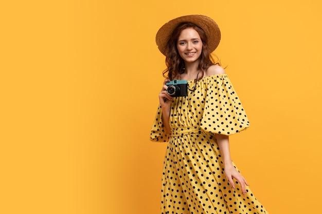 Reizende vrouw in strohoed en zomerjurk poseren met retro camera op geel