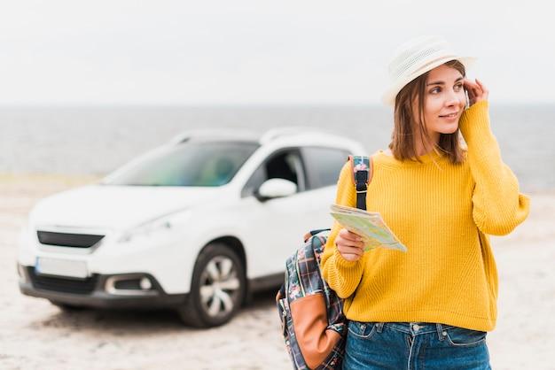 Reizende vrouw met auto op de achtergrond