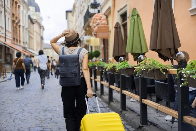 Reizende vrouwentoerist die in hoed met rugzak en koffer langs straat loopt