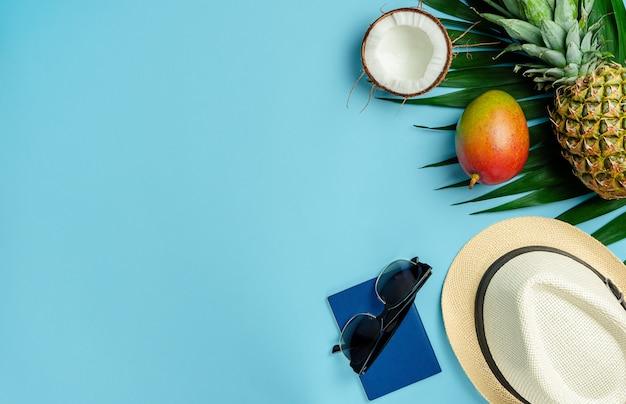 Reiziger accessoires en exotische vruchten op blauwe achtergrond. bovenaanzicht, kopieer ruimte.