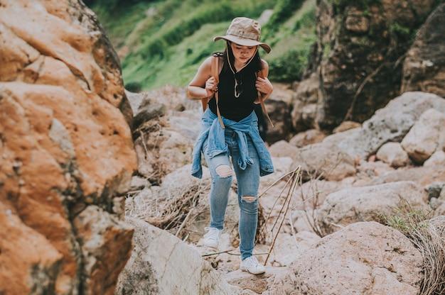 Reiziger aziatische vrouw die met rugzak op de rots door rivier in berg loopt