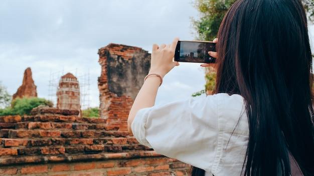 Reiziger aziatische vrouw die smartphone gebruikt om een foto te maken tijdens een vakantiereis in ayutthaya, thailand