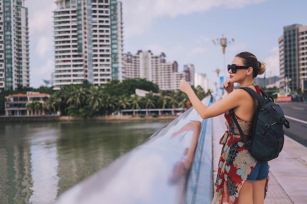 Reiziger blonde backpacker vrouw die in aziatische stad de stad in met wolkenkrabbers lopen. de aard van het reisavontuur in china, toeristen mooie bestemming azië, het concept van de de vakantiereis van de de zomervakantie