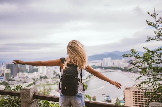 Reiziger blonde backpacker vrouw lopen met uitzicht op de binnenstad. reisavontuur in china, toeristische mooie bestemming azië, zomervakantie vakantiereis. vrijheid en gelukkige mensen concept