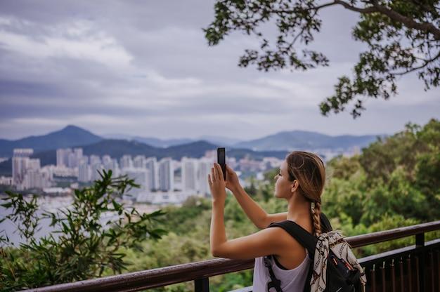 Reiziger blonde backpacker vrouw lopen nemen van foto's van observatiedek met uitzicht op de binnenstad. reisavontuur in china, toeristische mooie bestemming azië, zomervakantie vakantiereis