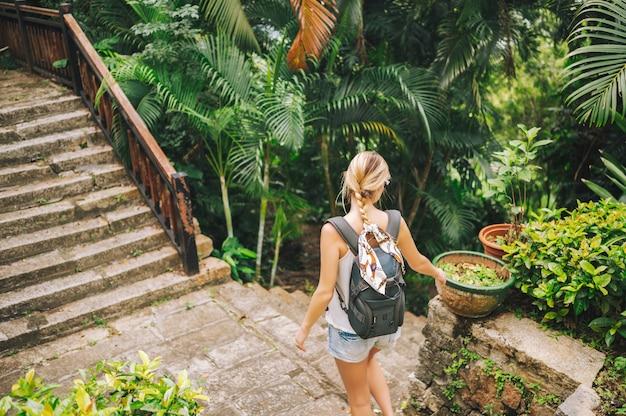 Reiziger blonde backpacker vrouw wandelen en ontdekken jungle tropisch park, reizen avontuur natuur in china, toeristische mooie bestemming azië, zomervakantie vakantie reis reisconcept