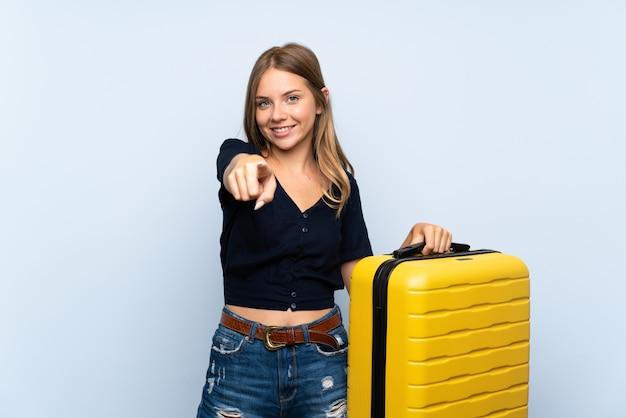 Reiziger blonde vrouw met koffer wijst vinger naar je met een zelfverzekerde uitdrukking