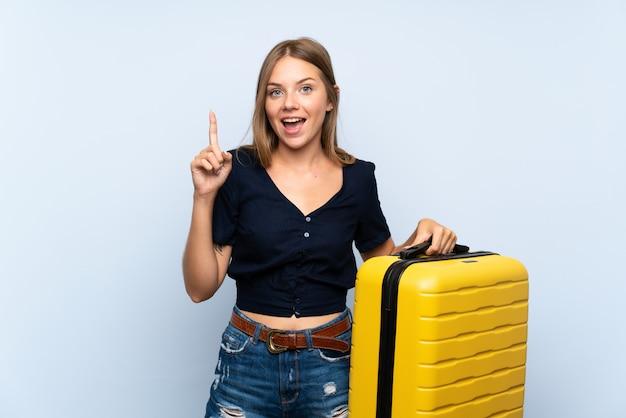 Reiziger blondevrouw die met koffer een groot idee benadrukken